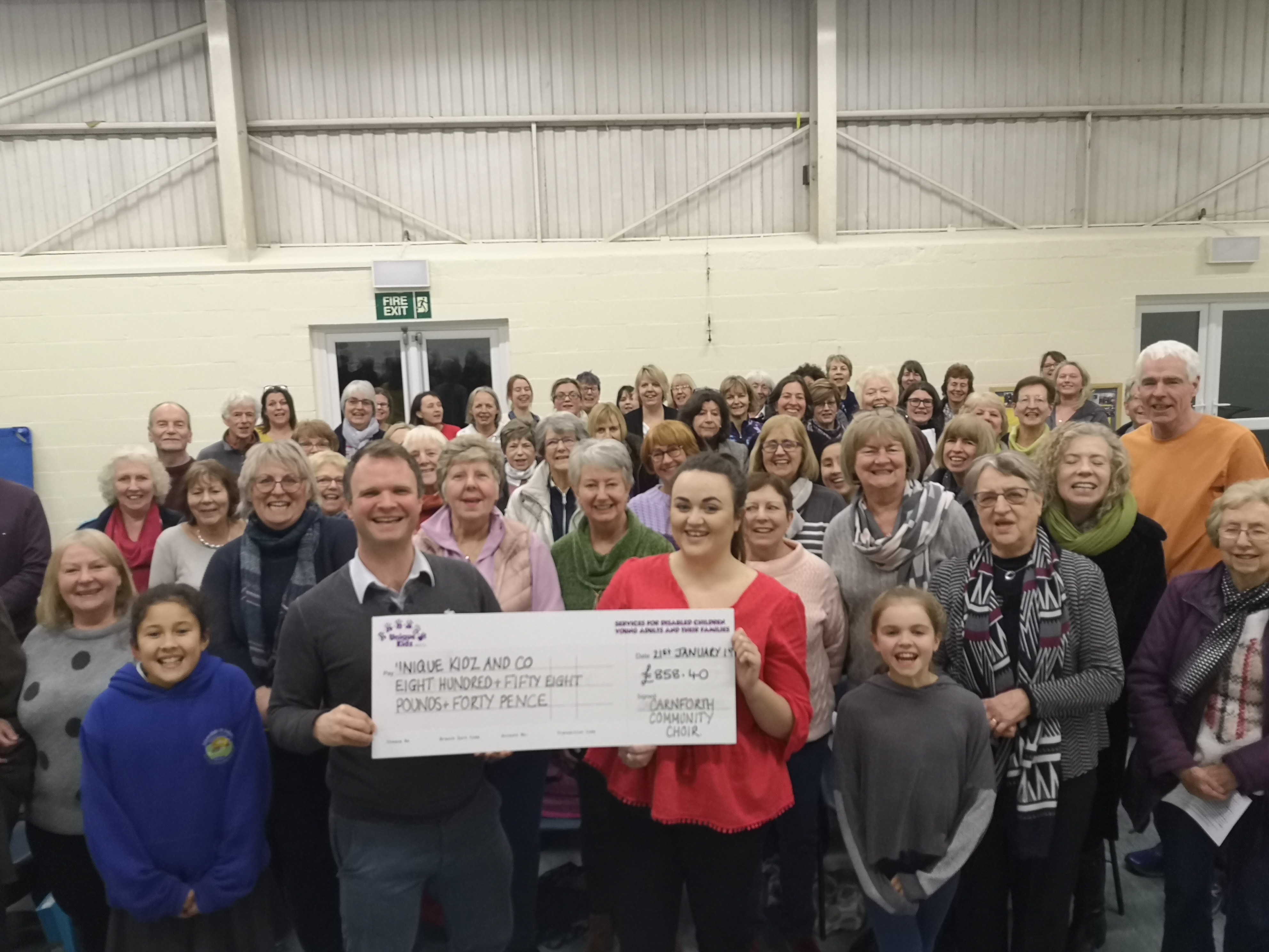 Carnforth Community Choir presenting Unique Kidz and Co with a cheque